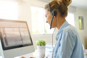 Mitarbeiterin mit Headset am Computer