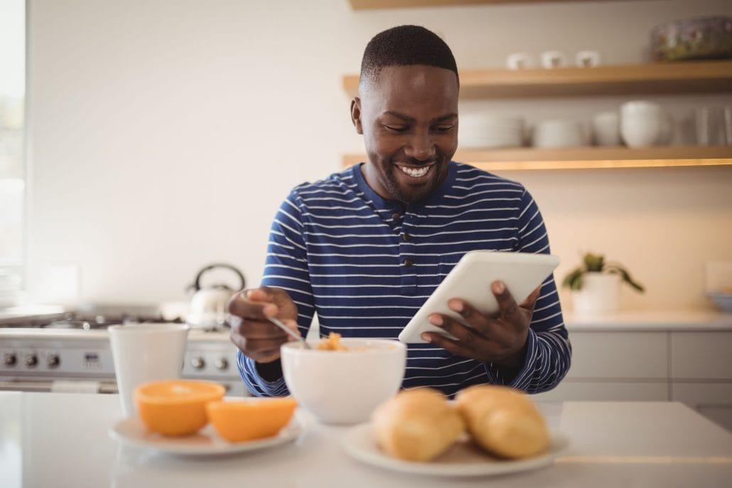 Das Bild zeigt einen neuen Mitarbeiter, der sein Preboarding zuhause beim Frühstück am Tablet absolviert.