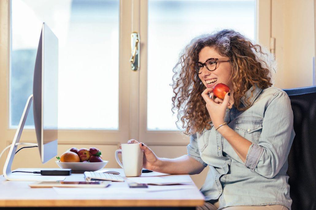 Eine neue Mitarbeitern die zuhause an ihrem Computer sitzt mit einem Apfel in der Hand und ihr Preboarding durch geht.