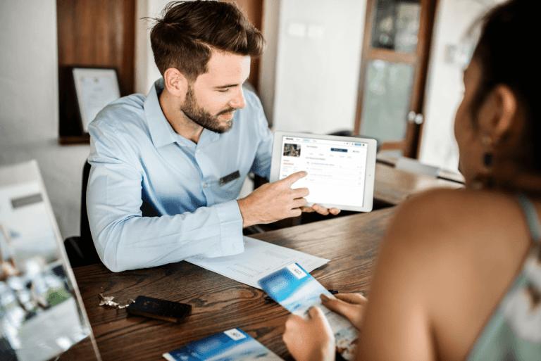 Ein Mitarbeiter zeigt einer neuen Mitarbeiterin das Onboarding mit der Talent Management Software elearnio am Tablet